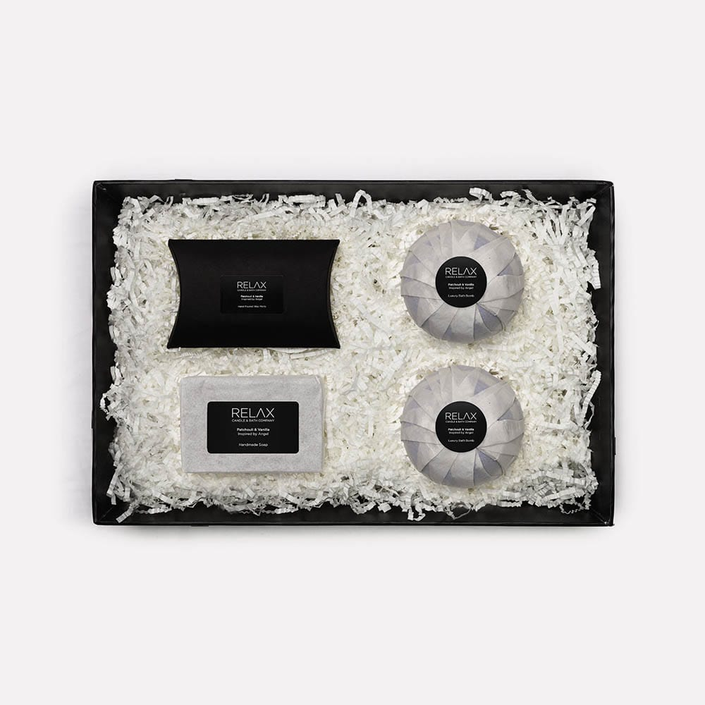 packaged gift set of four in white shredded paper on relax candle and bath