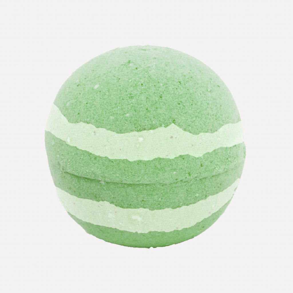 Unwrapped mint green and white bath bomb on relax candle and bath